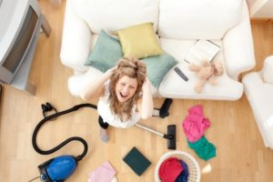 Stressed blond woman vacuuming the living-room
