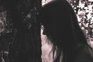 Sad woman leaning against tree
