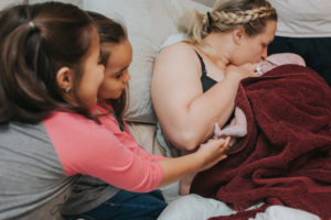 mom with newborn baby and girls at deliver