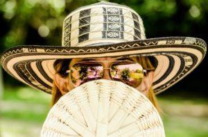 woman in hat with fan