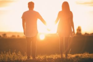 sunset couple holding hands