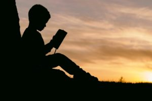 boy reading shadow silhouette sunset
