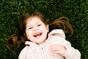 girl laughing in grass