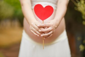 A mother holds a heart in front of her pregnant belly.