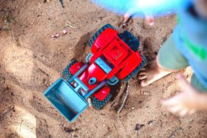 Kid Playing With Toy Truck In The Sand