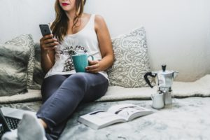 woman on a bed with coffee and a phone and a book