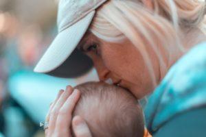 Woman kissing baby head