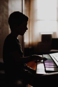 Child plays music on keyboard