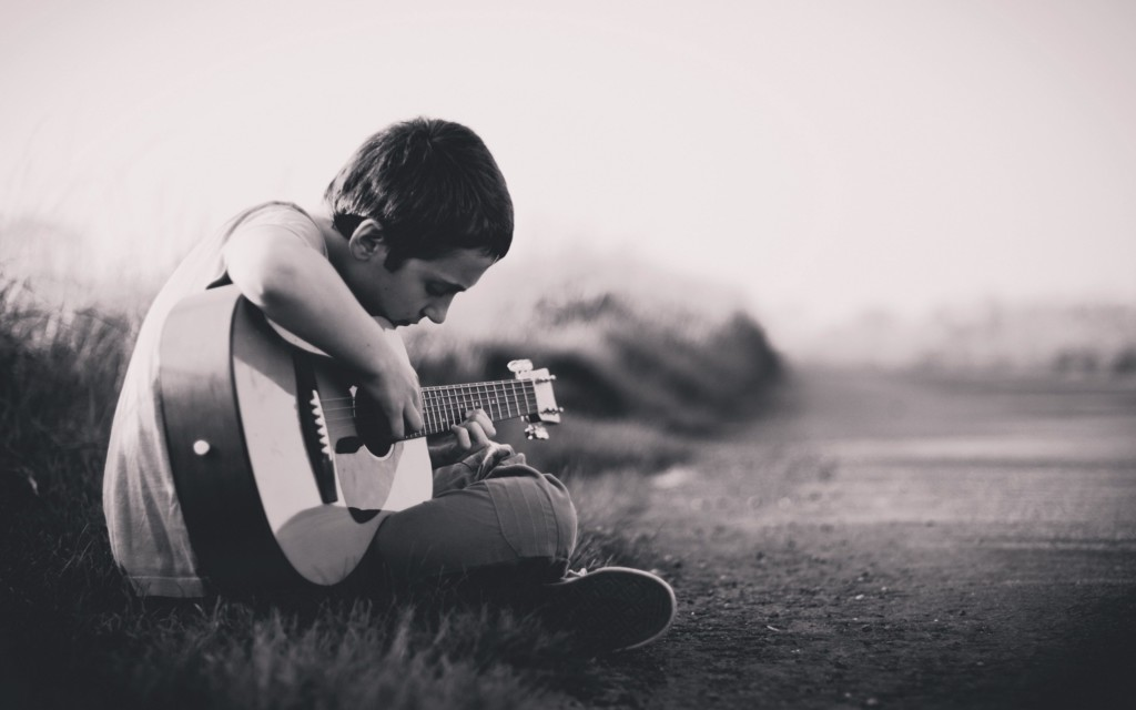 Black-and-white photo of child playing acoustic guitar