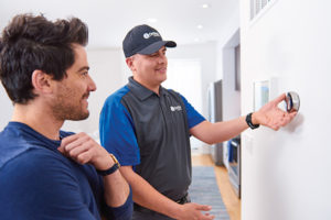 OnTech technician adjusting smart-home product in house