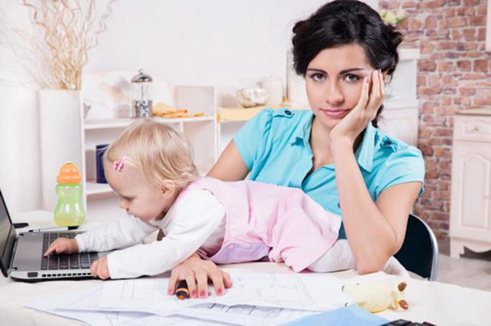 Mom trying to work from home with baby crawling across desk.