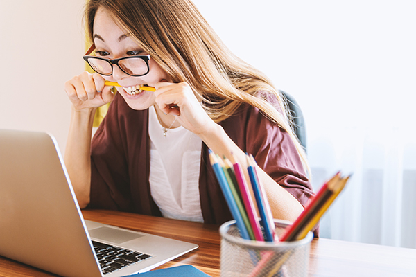 stressed lady at computer biting pencil