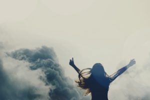 A woman holding her hands in the air feeling freedom from mental stress.