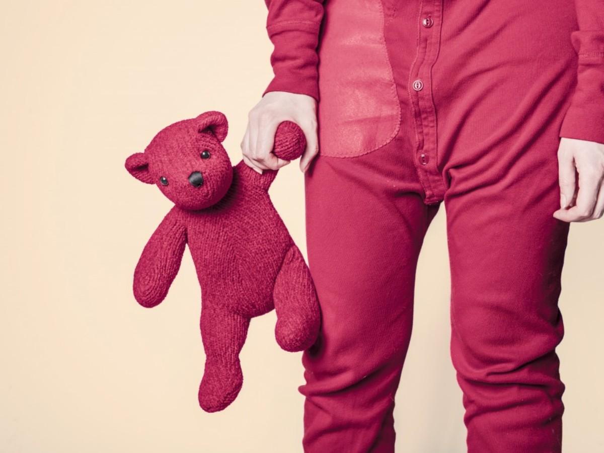 kid wearing pajamas holding bear