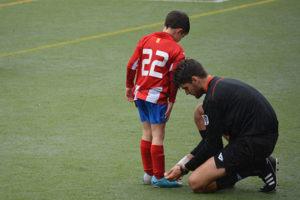 coach tying soccer player's shoe