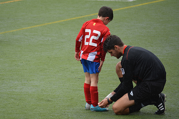 coach tying soccer player's shoe