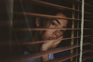 A woman looks through screens on a window.