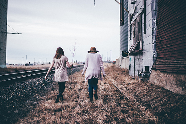 two women walking along the railroad tracks