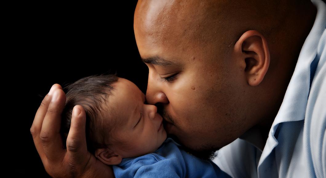 Dad kissing a newborn.