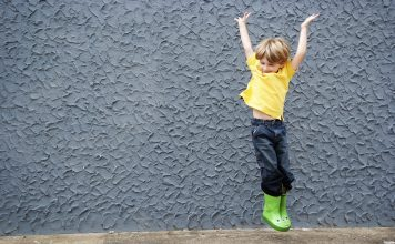 A boy jumps in a pair of green froggy rain boots.