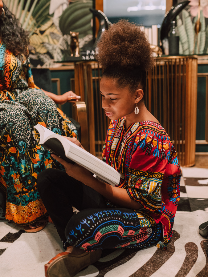 Black girl in African attire reading a book