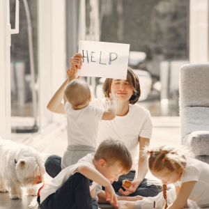 mom with 3 kids, holding up help sign