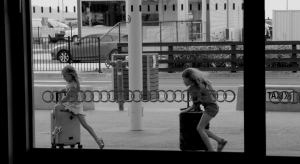 Two girls running through the airport with their suitcases.