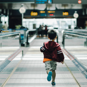 A young boy is running on the electric walkway at the airport.