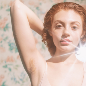 Woman is raising her arm to show underarm hair.